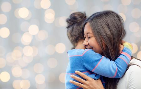 Photo for family, children, love and happy people concept - happy mother and daughter hugging over lights background - Royalty Free Image