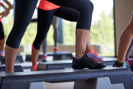 Foto de fitness, sport, people, step aerobics and lifestyle concept - close up of women legs exercising with steppers in gym - Imagen libre de derechos