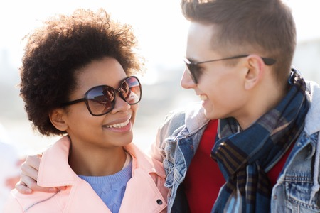 Photo for friendship, relations, tourism, travel and people concept - group of happy teenage friends or couple in sunglasses talking outdoors - Royalty Free Image