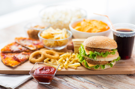 Photo for fast food and unhealthy eating concept - close up of hamburger or cheeseburger, deep-fried squid rings, french fries, drink and ketchup on wooden table - Royalty Free Image