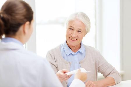 Foto de medicine, age, health care and people concept - doctor giving prescription to happy senior woman at hospital - Imagen libre de derechos