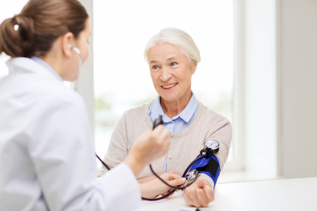 Foto de medicine, age, health care and people concept - doctor with tonometer checking happy senior woman blood pressure level at hospital - Imagen libre de derechos