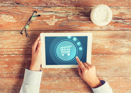 Photo pour business, people, online shopping and technology concept - close up of hands pointing finger to tablet pc computer screen with trolley icon, coffee cup and eyeglasses on table - image libre de droit