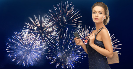 Foto de people, luxury, night life and finance concept - beautiful woman in evening dress with vip card and bag over firework on dark blue background - Imagen libre de derechos