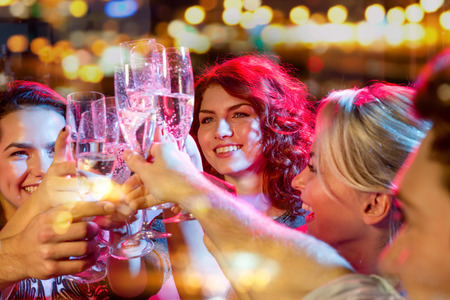 Foto per party, holidays, celebration, nightlife and people concept - smiling friends with glasses of champagne in club - Immagine Royalty Free