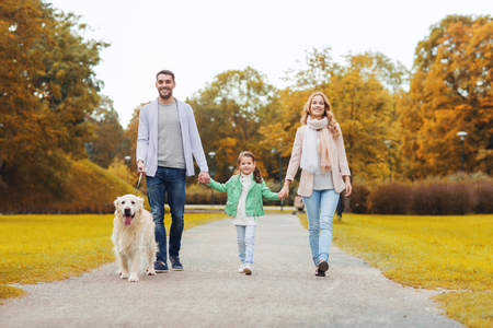 Photo pour family, pet, domestic animal, season and people concept - happy family with labrador retriever dog walking in autumn park - image libre de droit