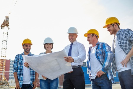 Foto de business, building, teamwork and people concept - group of builders and architects in hardhats with blueprint on construction site - Imagen libre de derechos