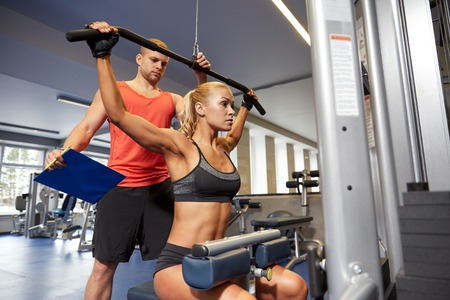 Foto de sport, fitness, teamwork and people concept - young woman flexing muscles on gym machine and personal trainer with clipboard - Imagen libre de derechos