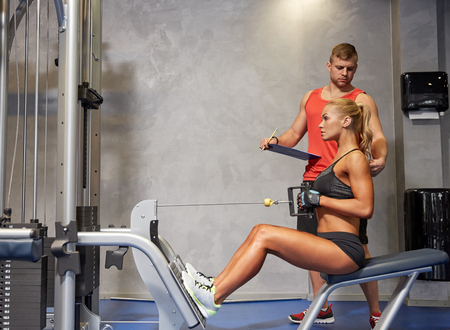 Foto de sport, fitness, teamwork and people concept - young woman and personal trainer flexing muscles on cable gym machine - Imagen libre de derechos