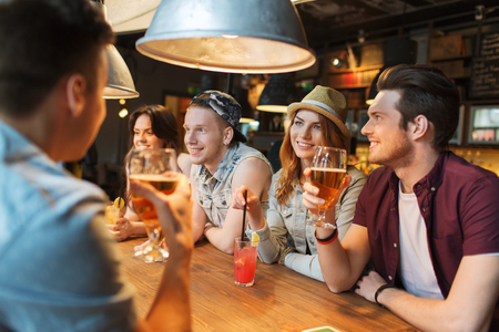 Photo for people, leisure, friendship and communication concept - group of happy smiling friends drinking beer and cocktails talking at bar or pub - Royalty Free Image