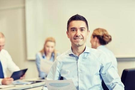 Foto de business, people and teamwork concept - smiling businessman with group of businesspeople meeting in office - Imagen libre de derechos