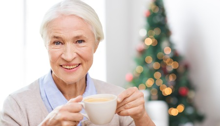 Photo pour age, drink, holidays, winter and people concept - happy smiling senior woman with cup of coffee at home over living room and christmas tree background - image libre de droit