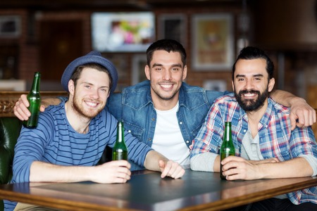 Photo pour people, leisure, friendship and bachelor party concept - happy male friends drinking bottled beer and hugging at bar or pub - image libre de droit