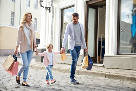 Photo pour sale, consumerism and people concept - happy family with little child and shopping bags in city - image libre de droit