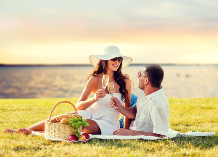 Foto de love, dating, people and holidays concept - happy couple drinking champagne on picnic over seaside sunset background - Imagen libre de derechos