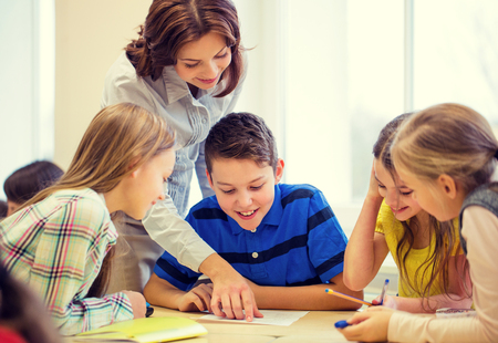 Photo for education, elementary school, learning and people concept - teacher helping school kids writing test in classroom - Royalty Free Image
