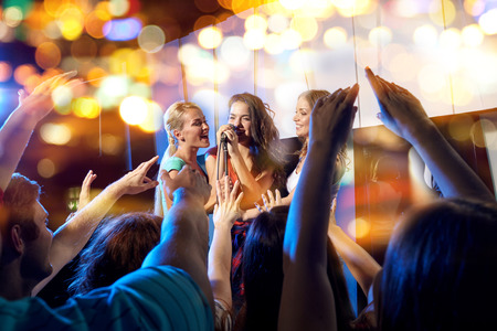 Photo for party, holidays, celebration, nightlife and people concept - happy young women singing karaoke in night club behind crowd of music fan - Royalty Free Image