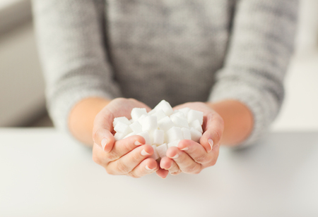 Foto per food, junk-food, diabetes and unhealthy eating concept - close up of white lump sugar in woman hands - Immagine Royalty Free