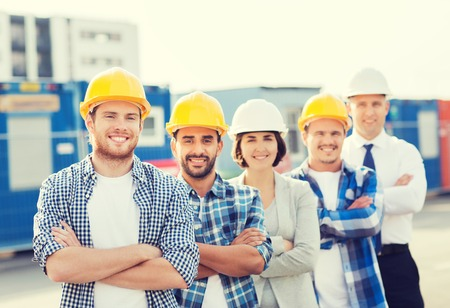 Photo pour business, building, teamwork and people concept - group of smiling builders in hardhats outdoors - image libre de droit