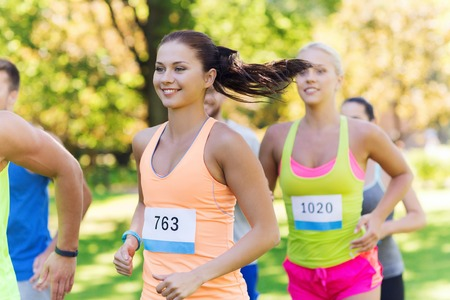 Photo pour fitness, sport, friendship, race and healthy lifestyle concept - group of happy teenage friends or sportsmen running marathon with badge numbers outdoors - image libre de droit