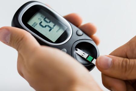 Foto de medicine, diabetes, glycemia, health care and people concept - close up of man checking blood sugar level by glucometer and test stripe at home - Imagen libre de derechos