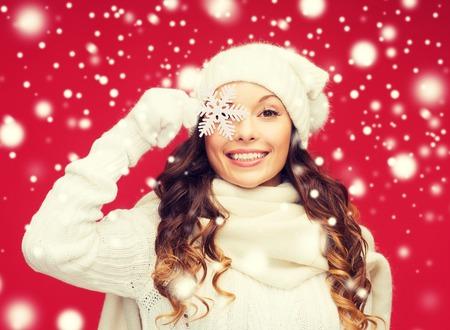 Foto de winter, people, happiness concept - woman in hat, muffler and gloves with big snowflake - Imagen libre de derechos