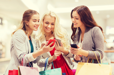 Photo pour sale, consumerism, technology and people concept - happy young women with smartphones and shopping bags in mall - image libre de droit