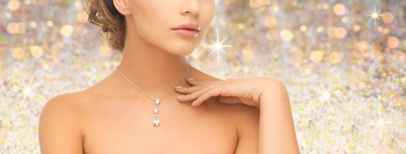 Photo pour people, jewelry, luxury, holidays and glamour concept - woman wearing shiny diamond pendant over golden lights background - image libre de droit