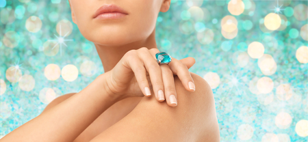 Photo pour people, jewelry, luxury and glamour concept - close up of woman hand and ring with precious gem over blue lights background - image libre de droit