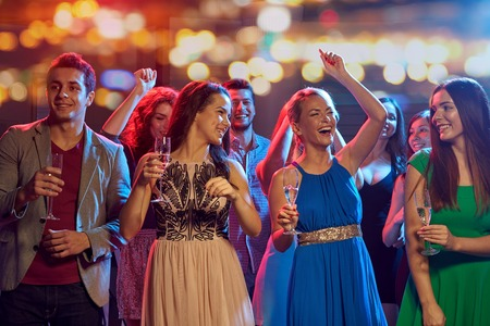 Foto de party, holidays, celebration, nightlife and people concept - happy friends with glasses of non-alcoholic champagne dancing at disco in nightclub - Imagen libre de derechos