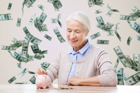 Foto de savings, finances, annuity insurance, retirement and people concept - smiling senior woman putting coins into piggy bank over money rain background - Imagen libre de derechos