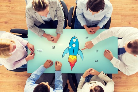 Photo pour business, people, startup, development and team work concept - close up of creative team sitting at table and pointing finger to rocket icon in office - image libre de droit