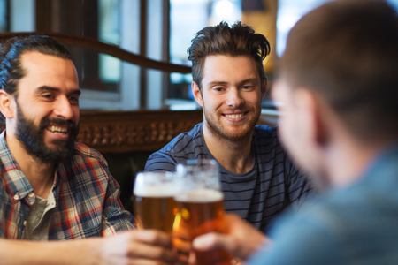 Photo pour people, men, leisure, friendship and celebration concept - happy male friends drinking beer and clinking glasses at bar or pub - image libre de droit