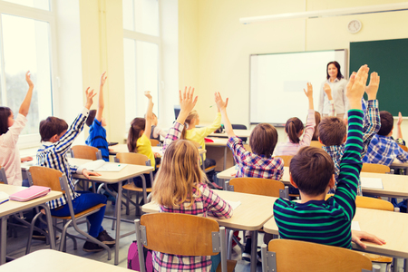 Photo for group of school kids with teacher sitting in classroom and raising hands - Royalty Free Image