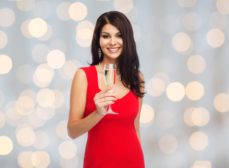 Photo for beautiful sexy woman in red dress with champagne glass over lights background - Royalty Free Image