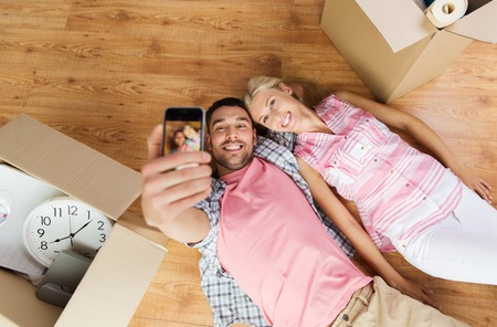 Photo pour happy couple taking selfie with smartphone and lying on floor among cardboard boxes at home - image libre de droit