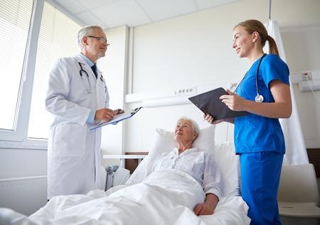 Foto de doctor and nurse with clipboards visiting senior patient woman at hospital ward - Imagen libre de derechos