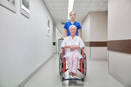 Foto de medicine, age, support, health care and people concept - nurse taking senior woman patient in wheelchair at hospital corridor - Imagen libre de derechos