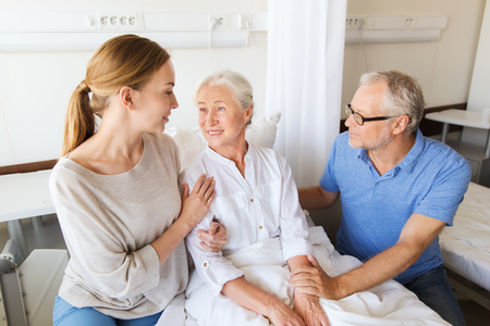 Photo for medicine, support, family health care and people concept - happy senior man and young woman visiting and cheering her grandmother lying in bed at hospital ward - Royalty Free Image