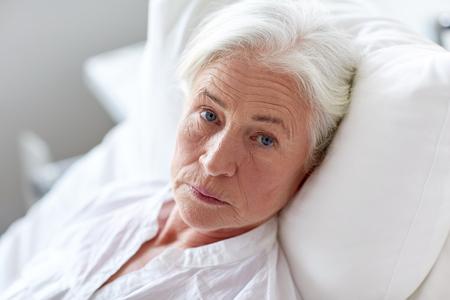 Foto de medicine, age, health care and people concept - senior woman patient lying in bed at hospital ward - Imagen libre de derechos