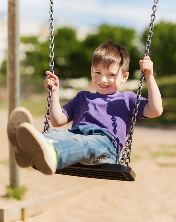 Photo for summer, childhood, leisure, friendship and people concept - happy little boy swinging on swing at children playground - Royalty Free Image