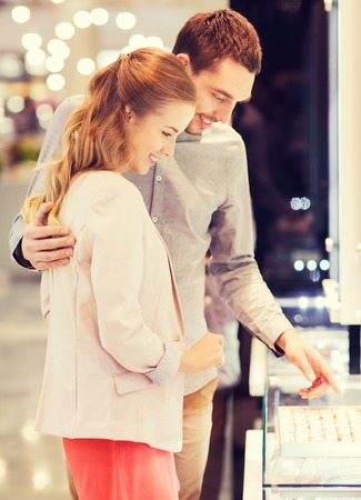 Photo pour sale, consumerism, shopping and people concept - happy couple choosing engagement ring at jewelry store in mall - image libre de droit