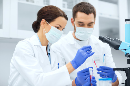 Foto de science, chemistry, technology, biology and people concept - young scientists with pipette and  test tube making research in clinical laboratory - Imagen libre de derechos