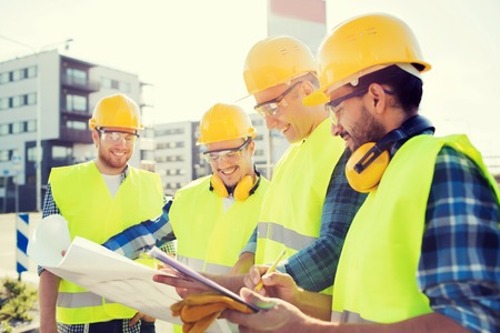 Foto de business, building, teamwork and people concept - group of smiling builders in hardhats with clipboard and blueprint outdoors - Imagen libre de derechos