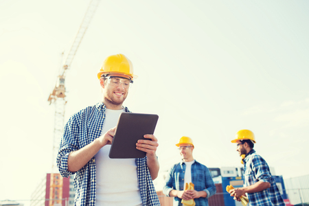 Foto de business, building, teamwork, technology and people concept - group of smiling builders in hardhats with tablet pc computer outdoors - Imagen libre de derechos
