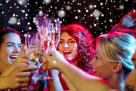 Photo for party, holidays, celebration, nightlife and people concept - smiling friends with glasses of non-alcoholic champagne in club - Royalty Free Image