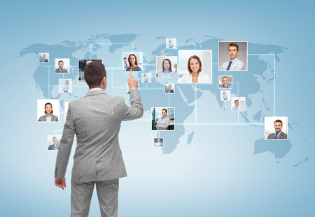 Photo pour business, people, communication and technology concept - businessman pointing finger to contact icons on world map over blue background from back - image libre de droit