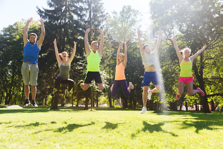 Foto de fitness, sport, friendship and healthy lifestyle concept - group of happy teenage friends or sportsmen jumping high outdoors - Imagen libre de derechos
