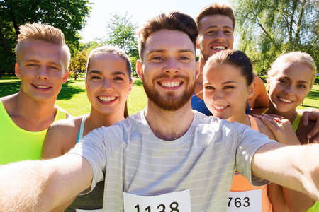 fitness, sport, friendship, technology and healthy lifestyle concept - group of happy teenage friends with racing badge numbers taking selfie by smartphone at marathon outdoors