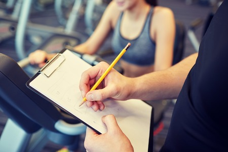 Foto de sport, fitness, lifestyle, technology and people concept - close up of trainer hands with clipboard writing and woman working out on exercise bike in gym - Imagen libre de derechos